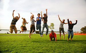 A family of kids and adults jumping in the air on the grass