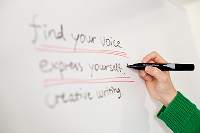 A hand writing: find your voice, express yourself, creating writing