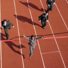 a group of people running around a track in business suits