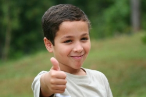 A boy smiling and holding up a thumbs up