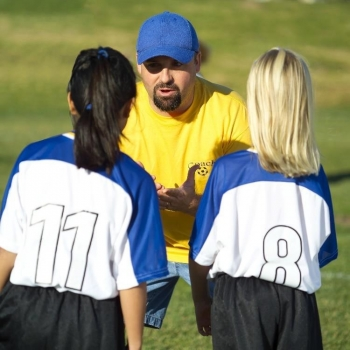 A coach speaking to two young athletes.