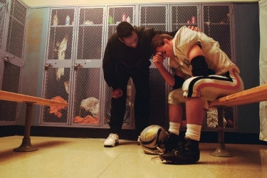 A coach consoling a football player.