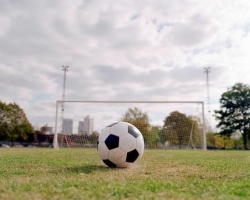 A soccer ball lined up in front of a goal.