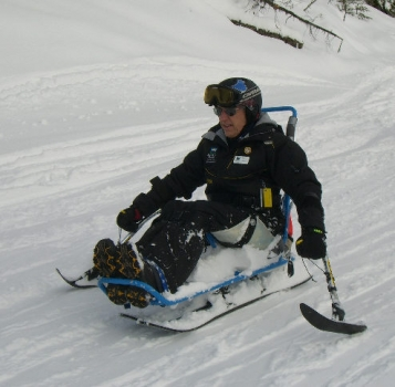 Dick Taylor demonstrates sit-skiing to his instructors at Sun Peaks
