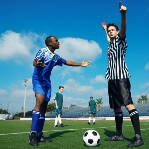 A referee giving a soccer player a red card.