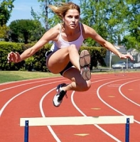 athlete jumping over a hurdle