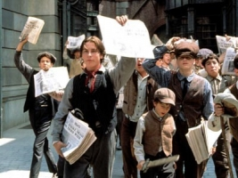 a group of boys holding up newspapers