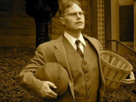 James Naismith, who created the game of basketball in 1891, holding a ball and basket