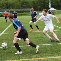 Two soccer players going for the ball