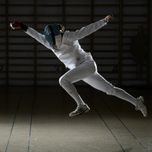 A fencer mid-strike in the air