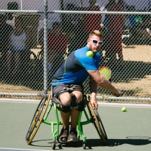 Wheelchair tennis athlete swinging at the ball in mid-air