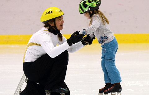 Skating coach teaching a young girl