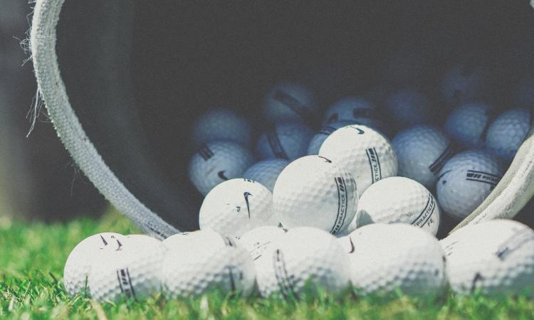 Golf balls falling out of bucket