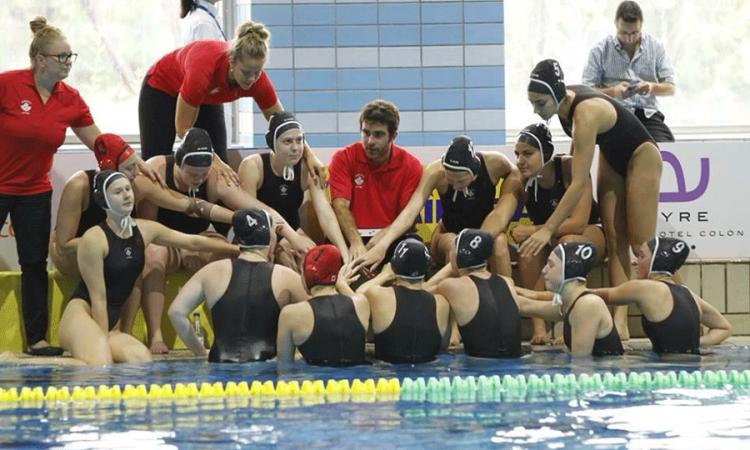 Photo of Angela at the pool deck coaching her water polo team
